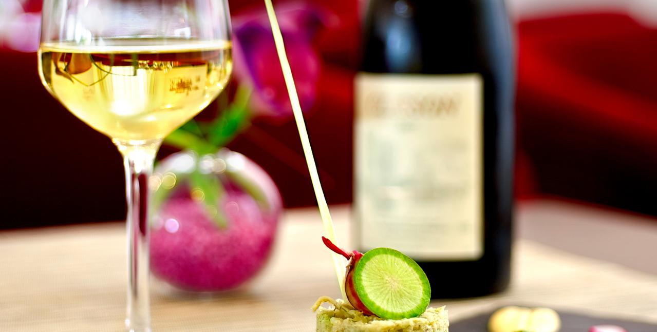 Un verre de vin blanc, sa bouteille et un met d'apéritif sur une table